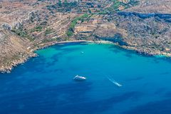 Mgiebah海湾,偏僻的小海湾容易接近由一条陡峭,岩石道路,用沙滩和天蓝色的土耳其玉色水 Mellieha,马耳他 图库摄影