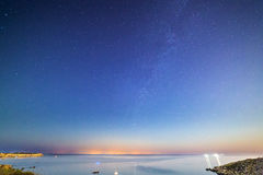 Mgiebah Bay at Night. Long exposure of Mgiebah Bay in Malta on a clear summer night. Street lights from Sicily can be clearly seen in the background on the stock photography