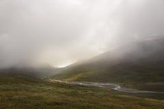 Mglista i chmurna sceneria w zielonej żyznej rzecznej dolinie tworzy markotną scenę Zdjęcie Stock