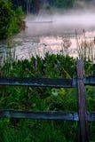 Mglistego ranku Jeziorna scena z ogrodzeniem Fotografia Stock