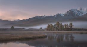 Mglisty jesień ranek nakrywał góry, malowniczy halny jezioro na tle śnieg Obrazy Royalty Free