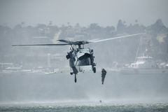MH-60S Knighthawk Helicopter. A US Navy MH-60S Knighthawk Helicopter drops a rescuer in the water during a demonstration on lifesaving techniques, SEAL Royalty Free Stock Images