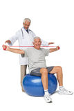Mhysiotherapist looking at senior man sit on exercise ball with yoga belt. Male physiotherapist looking at senior men sit on exercise ball with yoga belt over Stock Photography