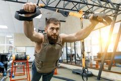 Mięśniowy brodaty mężczyzna ubierał w wojskowy obciążającej opancerzonej kamizelce robi ćwiczeniom używać patka systemy w gym Spo obraz stock