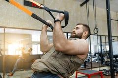 Mięśniowy brodaty mężczyzna ubierał w wojskowy obciążającej opancerzonej kamizelce robi ćwiczeniom używać patka systemy w gym Spo fotografia stock