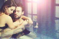 Mięśniowy mężczyzna i seksowna kobieta w błękitnym basenie z koktajlem zdjęcie royalty free
