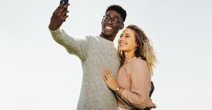Międzyrasowa para na wakacje bierze selfie fotografia stock