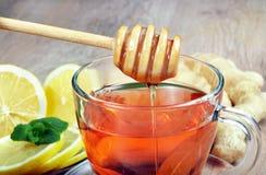 Miód, imbir, cytryna i filiżanka herbata na drewnianym stole, zimno grypa lekarstwo obraz royalty free