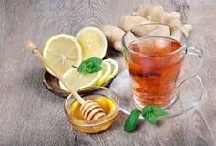 Miód, imbir, cytryna i filiżanka herbata na drewnianym stole, zimno grypa lekarstwo zdjęcia royalty free
