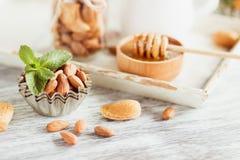 Miód w drewnianym pucharze, nowych liściach, migdałach i słoju z mlekiem na drewnianej tacy, Fotografia Stock