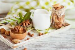 Miód w drewnianym pucharze, nowych liściach, migdałach i słoju z mlekiem na drewnianej tacy, Zdjęcie Stock