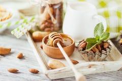 Miód w pucharze, muesli, nowych liściach, migdałach i słoju z mlekiem na drewnianej tacy, Obraz Royalty Free