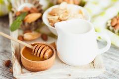 Miód w pucharze, muesli, nowych liściach, migdałach i słoju z mlekiem na drewnianej tacy, Zdjęcia Stock