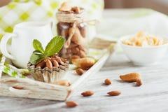 Miód w pucharze, muesli, nowych liściach, migdałach i słoju z mlekiem na drewnianej tacy, Zdjęcie Stock
