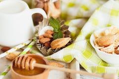 Miód w pucharze, muesli, nowych liściach, migdałach i słoju z mlekiem na drewnianej tacy, Obraz Stock