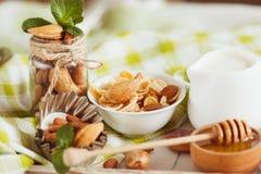 Miód w pucharze, muesli, nowych liściach, migdałach i słoju z mlekiem na drewnianej tacy, Fotografia Stock