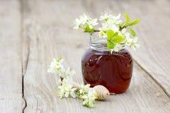 Miód w słoju, kwiatach i miodowej chochli, zdjęcia royalty free