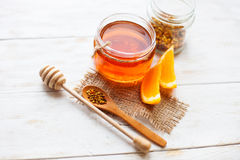 Miód w szklanej pomarańcze na białym tle drewnianym i słoju Obraz Royalty Free