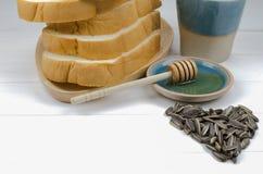 Miód z stertą chleb, słonecznikowi ziarna i filiżanka mleko, Zdjęcie Stock