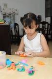 Miúdo asiático que joga com massa de pão Fotos de Stock