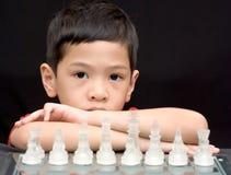 Miúdo asiático que joga a xadrez Imagem de Stock
