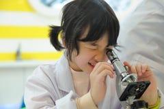 Miúdo asiático que olha no microscópio Fotografia de Stock