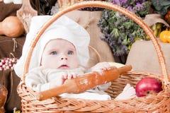 Miúdo bonito como um cozinheiro chefe que senta-se em uma cesta Fotos de Stock Royalty Free