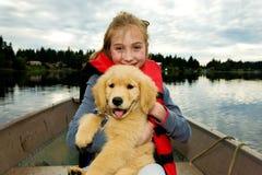 Miúdo bonito e um filhote de cachorro em um lago Fotos de Stock Royalty Free