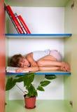 Miúdo cansado que dorme na prateleira com um livro em vez de um descanso Imagem de Stock Royalty Free