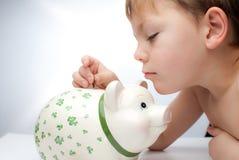 Miúdo com um banco piggy Foto de Stock Royalty Free