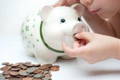 Miúdo com um banco piggy Fotografia de Stock Royalty Free