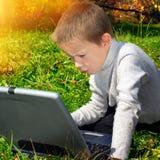 Miúdo com um portátil Foto de Stock