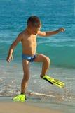 Miúdo engraçado que anda as aletas desgastando da praia Imagem de Stock