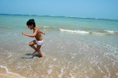 Miúdo feliz na praia foto de stock