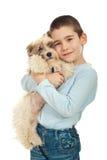 Miúdo feliz que prende seu filhote de cachorro Imagem de Stock Royalty Free