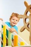 Miúdo feliz que senta-se nas escadas do campo de jogos Fotografia de Stock