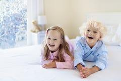 Miúdo na cama Janela do inverno Criança em casa pela neve fotos de stock royalty free