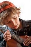 Miúdo que aprende jogar a guitarra Fotos de Stock