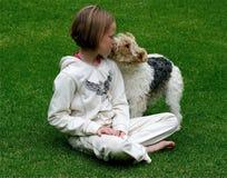 Miúdo que beija seu filhote de cachorro imagem de stock royalty free