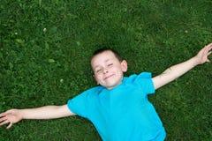 Miúdo que encontra-se na grama Foto de Stock Royalty Free