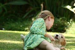 Miúdo que joga com filhote de cachorro Fotos de Stock Royalty Free
