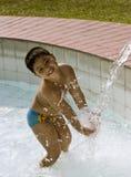 Miúdo que joga com fonte Foto de Stock