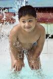 Miúdo que joga com waterfountain Fotos de Stock