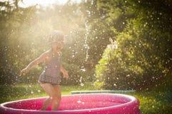 Miúdo que joga na água Fotos de Stock Royalty Free