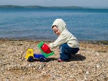 Miúdo que joga na praia Fotografia de Stock