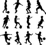 Miúdo que joga o futebol Fotografia de Stock