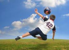 Miúdo que joga o futebol fora Fotos de Stock