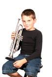Miúdo que joga a trombeta da terra arrendada Foto de Stock