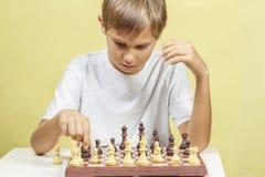 Miúdo que joga a xadrez Menino que olha a placa de xadrez e que pensa sobre sua estratégia fotos de stock