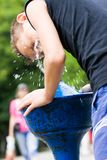 Miúdo que refrigera com água de uma torneira da rua fotografia de stock royalty free